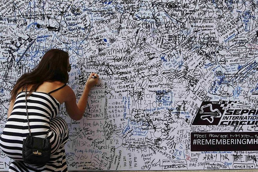 A woman writes on a wall dedicated to the passengers of the missing Malaysia Airlines flight MH370 before the Malaysian F1 Grand Prix at Sepang International Circuit outside Kuala Lumpur, on March 30, 2014. -- PHOTO: AFP