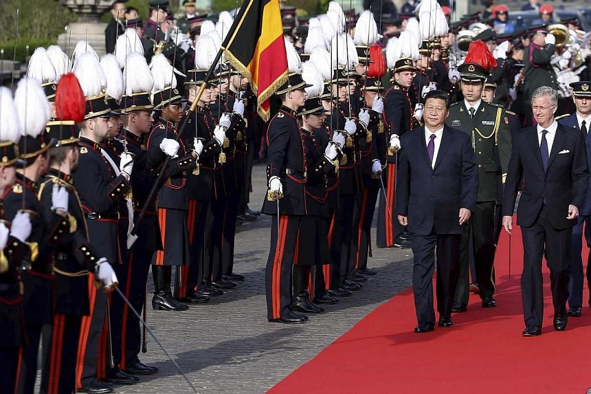Belgium's King Philippe (front right) and China's President Xi Jinping review honour guards during an official ceremony in Brussels March 30, 2014. Xi Jinping received a royal welcome and an honorary knighthood in Brussels on Sunday, March 30, 2014 a