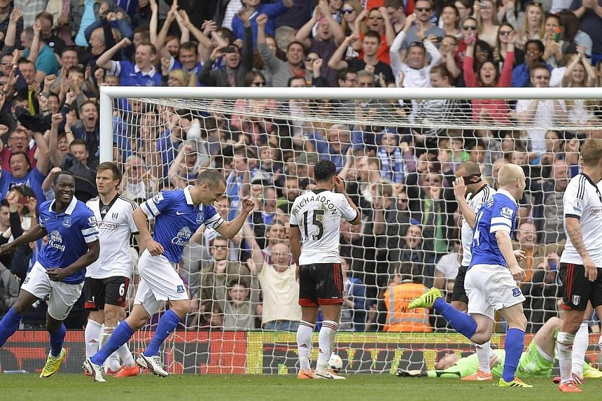 Everton's players celebrate after Fulham's goalkeeper David Stockdale (lying on ground) scored an own goal during their English Premier League soccer match at Craven Cottage in London March 30, 2014. Everton improved their outside chance of snatching