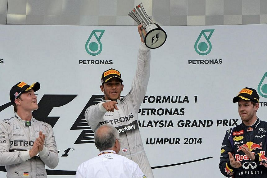 Mercedes driver Lewis Hamilton of Britain holds up the winner's trophy as he celebrates his victory with teammate Nico Rosberg of Germany (left), who finished second, third-placed Red Bull driver Sebastian Vettel (right) of Germany and Malaysian Prim