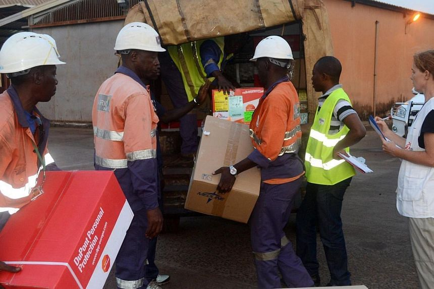 Workers load boxes of material including protection gear for the NGO Medecins sans Frontieres (Doctors without borders-MSF) at the airport of Conakry on March 29, 2014. Guinea raced on Saturday, March 29, 2014 to contain a deadly Ebola epidemic sprea