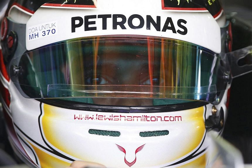 Mercedes Formula One driver Lewis Hamilton of Britain waits in his car during the first practice session of the Malaysian F1 Grand Prix at Sepang International Circuit outside Kuala Lumpur on March 28, 2014. He is wearing a helmet with a sticker in M