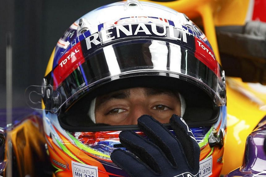 "Red Bull Formula One driver Daniel Ricciardo of Australia adjusts his helmet with the sticker ""Doa Untuk MH370"" as he waits in his car during the third practice session of the Malaysian F1 Grand Prix at Sepang International Circuit outside Kuala Lump"