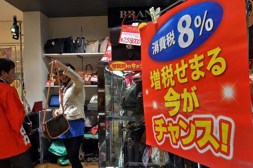 A customer checks products at a shop in Chiba, suburban Tokyo on March 29, 2014. Japan is bracing for its first sales tax rise in years, with last minute shoppers buying up a host of goods from gold to ice cream, as the government tries to tackl