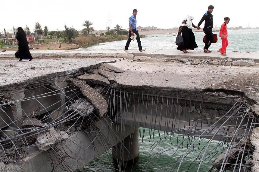 Iraqis walk past a gaping hole following a suicide bombing along the center of the al-Hoz Bridge which lies across the Euphrates River linking the southern district with the central district of the city of Ramadi, west of the capital Baghdad on Sunda