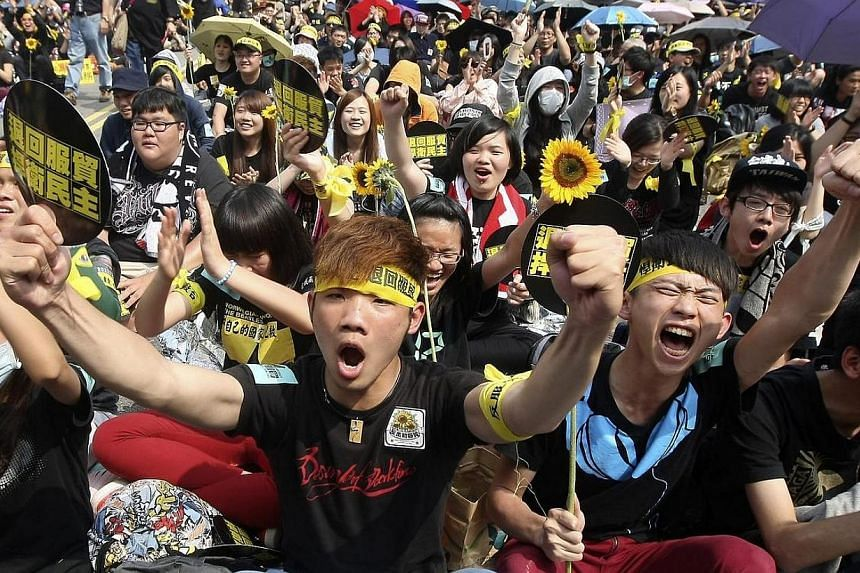 Demonstrators shout slogans in front of the Presidential Office in Taipei on Sunday, March 30, 2014. Tens of thousands of Taiwanese protesters took to the streets in Taipei on Sunday in a bid to pressure embattled President Ma Ying-jeou to retra