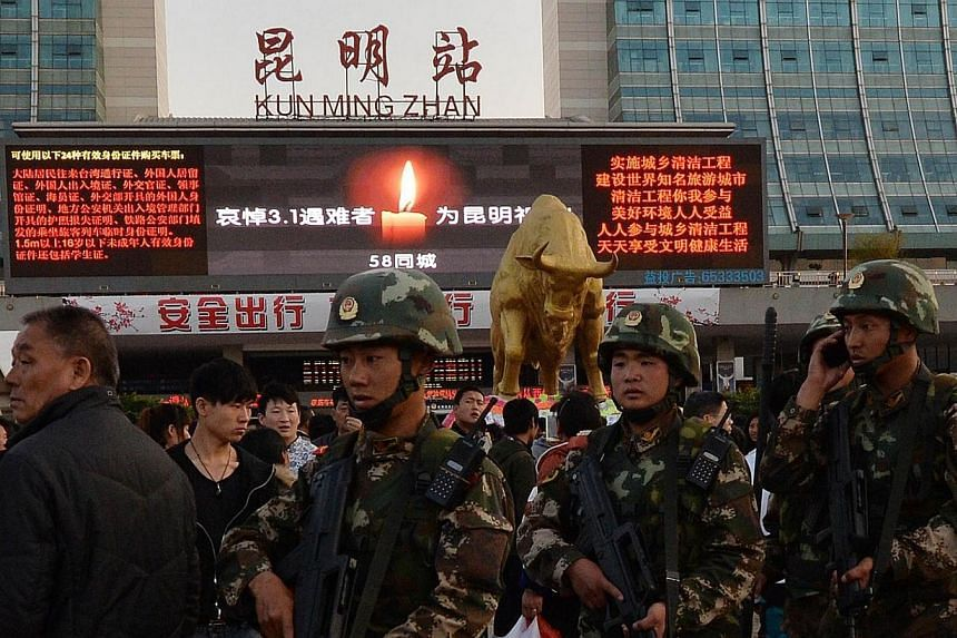 Chinese paramilitary police patrol outside the scene of the attack at the main train station in Kunming, Yunnan Province on March 3, 2014.China has laid out the charges against four suspects captured after a brutal railway station attack that k