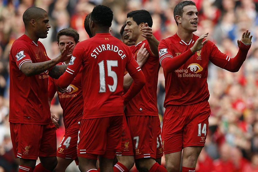 Liverpool's Jordan Henderson (right) celebrates scoring with teamates during their English Premier League soccer match against Tottenham Hotspur at Anfield in Liverpool, northern England, on March 30, 2014. -- PHOTO: REUTERS