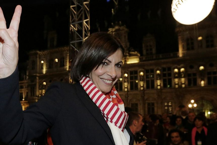 Ms Anne Hidalgo, current Paris city deputy mayor and Socialist Party candidate in the mayoral election, gives the V sign outside Paris town hall after her victory in the second round in the French mayoral elections in Paris on March 30, 2014. -- PHOT