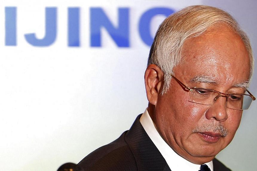 Malaysian Prime Minister Najib Razak leaves the room after addressing reporters about the missing Malaysia Airlines flight MH370 at Kuala Lumpur International Airport March 15, 2014. Malaysian Prime Minister Najib Razak will travel to Perth on Wednes