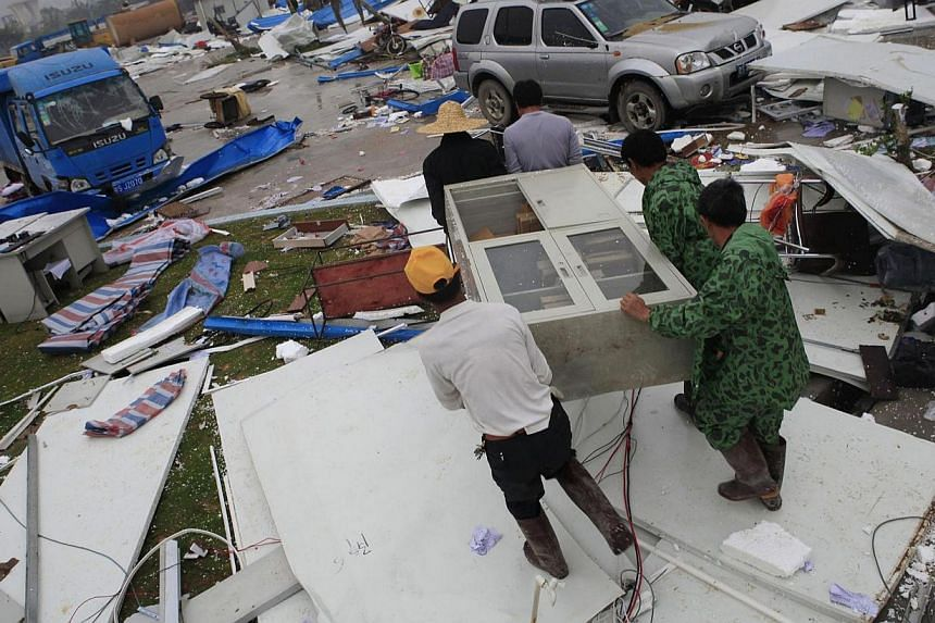 Workers carry a cabinet as they clean up amid debris of temporary sheds at a construction site after being hit by a heavy rainstorm in Dongguan, Guangdong province March 30, 2014. At least 16 people were killed in rain and hailstorms that triggered f