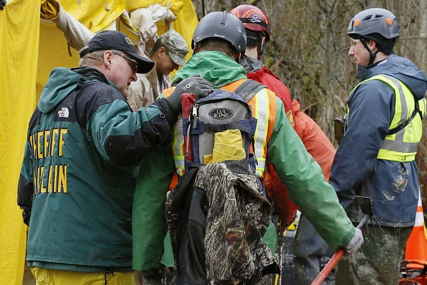 A sheriff's department chaplain (left) comforts a rescue worker heading into the decontamination tent after searching for victims of a mudslide in Oso, Washington, on March 30, 2014. -- PHOTO: REUTERS