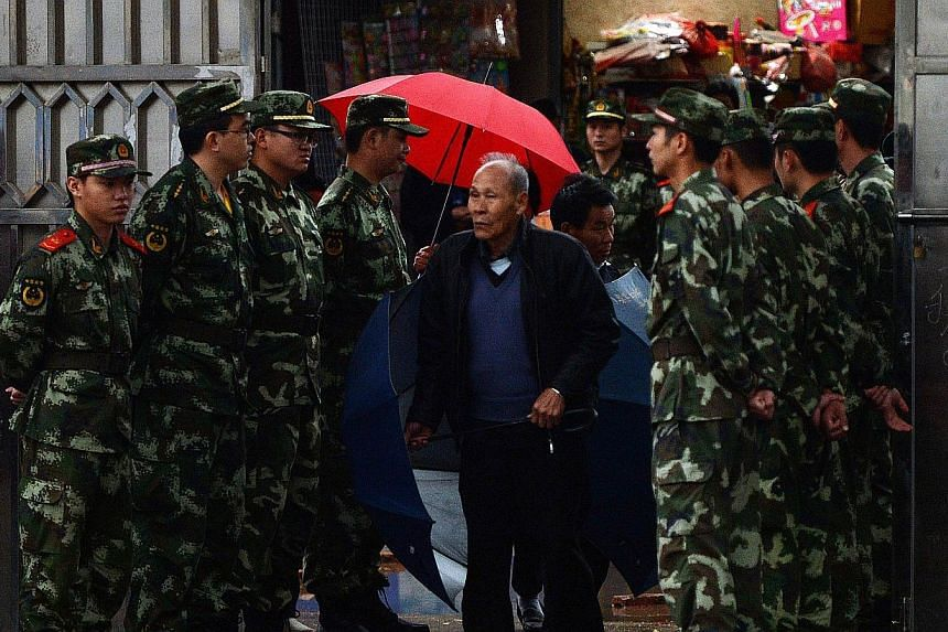 Local residents walk past Chinese paramilitary police as they arrive to vote during elections in the village of Wukan on March 31, 2014.Drenched voters in the Chinese village of Wukan, which held landmark democratic elections after rebelling ag
