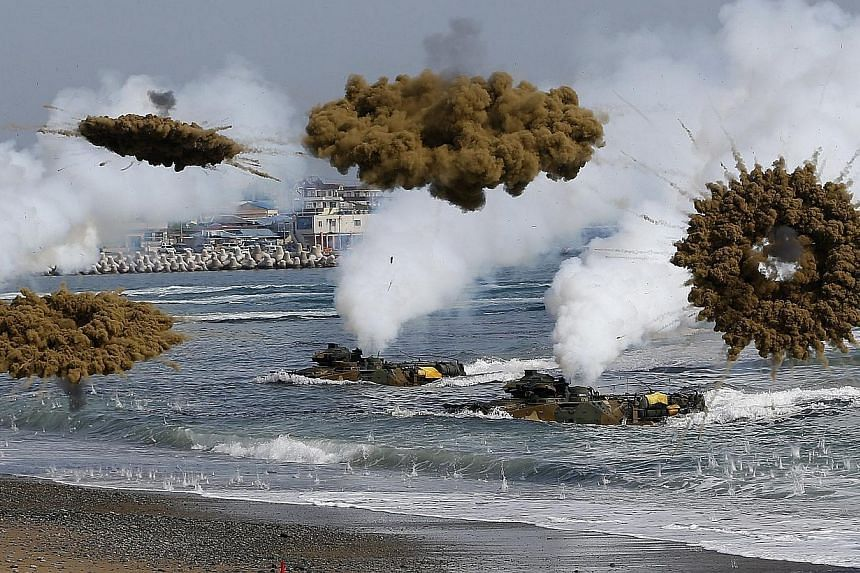 Amphibious assault vehicles of the South Korean Marine Corps throw smoke bombs as they move to land on shore during a U.S.-South Korea joint landing operation drill in Pohang March 31, 2014. The two Koreas traded hundreds of rounds of live artil