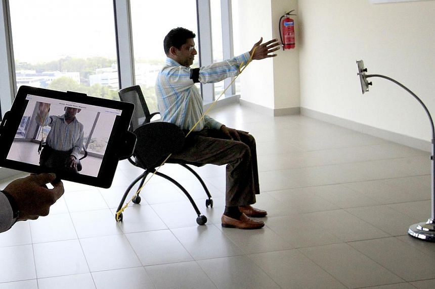 NUH staff, act as patient using an Ipad to demonstrate the exercising, the technology works that NUH is introducing a new telehealth system to monitor the recovery of stroke patients at home. Stroke patients may now be able to recover in the comfort