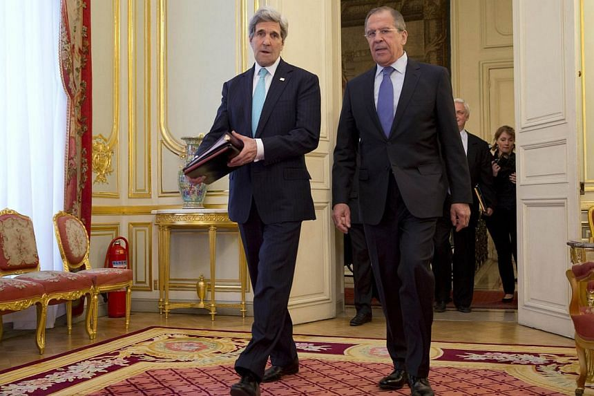 United States Secretary of State John Kerry (left) walks with Russian Foreign Minister Sergei Lavrov at the Russian Ambassador's residence in Paris on March 30, 2014. -- PHOTO: REUTERS