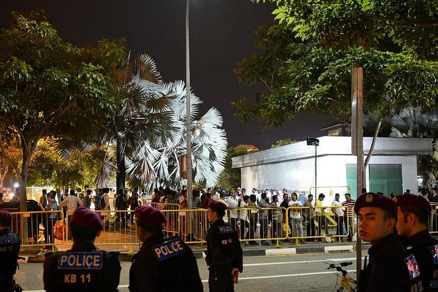 Members of the Singapore Police Force Special Operations Command stand along Tekka Lane in front of cordons which have been put in place at the dormitory bus waiting area on Jan 26, 2014.  -- ST FILE PHOTO: MARK CHEONG
