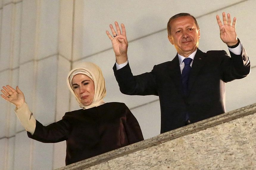Turkish Prime Minister Tayyip Erdogan, accompanied by his wife Emine, greets his supporters at the AK Party headquarters in Ankara on March 30, 2014. -- PHOTO: REUTERS