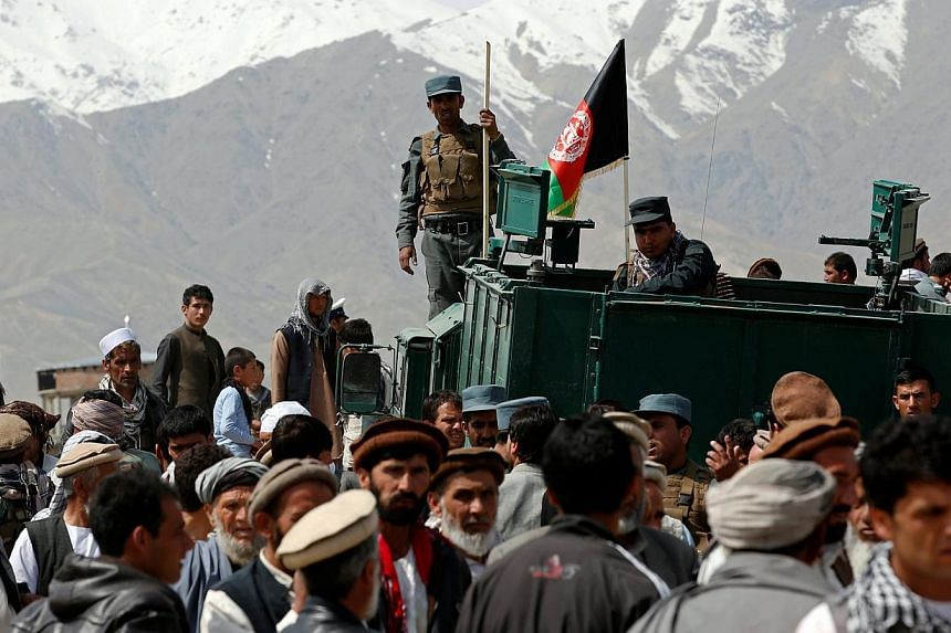 Policemen keep watch during an election campaign rally by Afghan presidential candidate Zalmai Rassoul in Bagram on April 1, 2014.Afghan security forces have seized more than 22 tonnes of explosives, enough to make hundreds of bombs, the interi