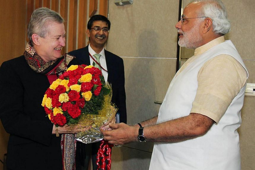 In this photo taken earlier this year, Chief Minister of the western Indian state of Gujarat and Bharatiya Janata Party (BJP) prime ministerial candidate Narendra Modi (R) presents a bouquet of flowers to US Ambassador to India Nancy Powell (L) as th