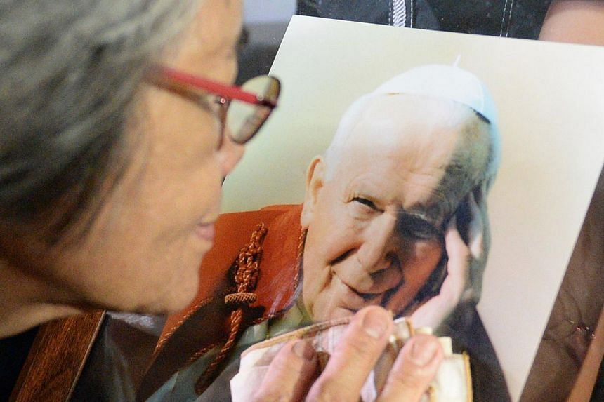 A Roman Catholic woman from the Philippines touches a relic of the late Pope John Paul II on display at a chapel in Manila on April 1, 2014. -- PHOTO: AFP