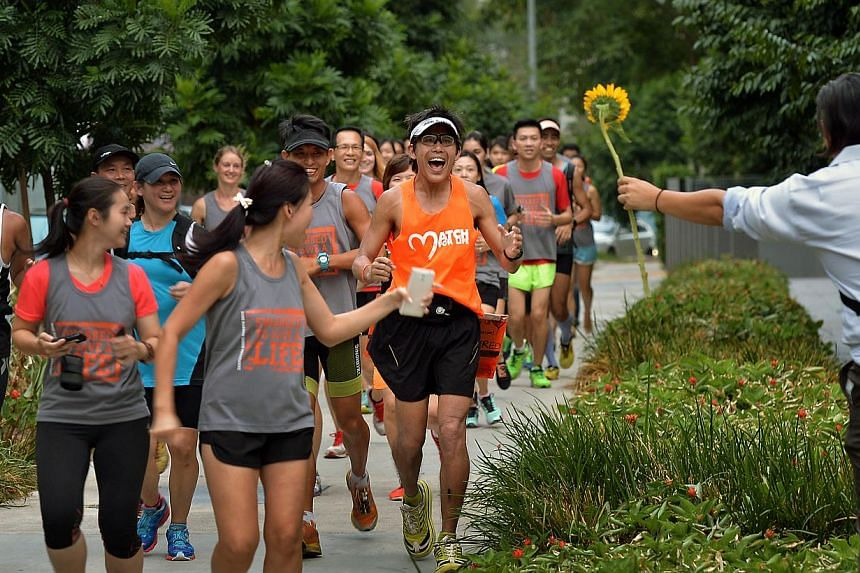 A supporter handing Mr Gerrard Lin a sunflower at the end of his 30th marathon yesterday at Novena Specialist Centre. The martial arts instructor hopes to sign up 1,302 donors – one for every km he ran during his March Madness – for the bone marr