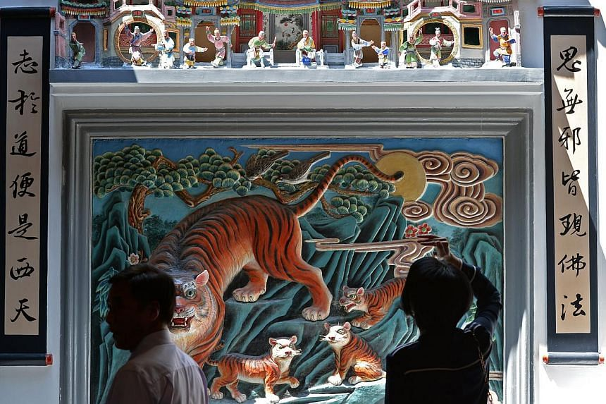 Plaster art work (above) of tigers and dragons are a common feature on the walls of Teochew temples. -- ST PHOTOS: DESMOND FOO