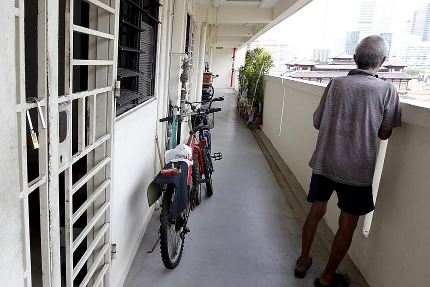 An elderly man standing outside the common corridor of a HDB flat. -- BT FILE PHOTO: YEN MENG JIIN
