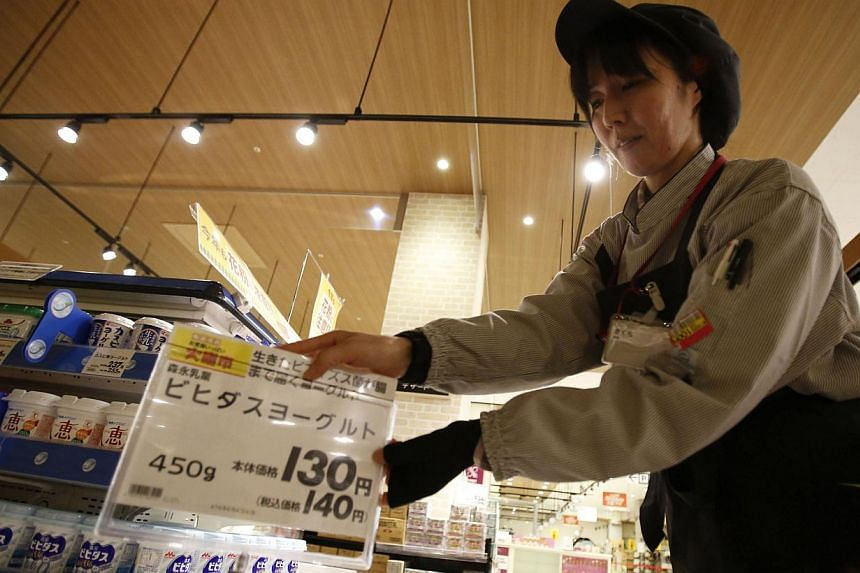 A staff of Aeon Co Ltd's supermarket changes a price tag due to a sales tax hike, ahead of the store's opening hours at a supermarket in Chiba, east of Tokyo, on April 1, 2014. -- PHOTO: REUTERS