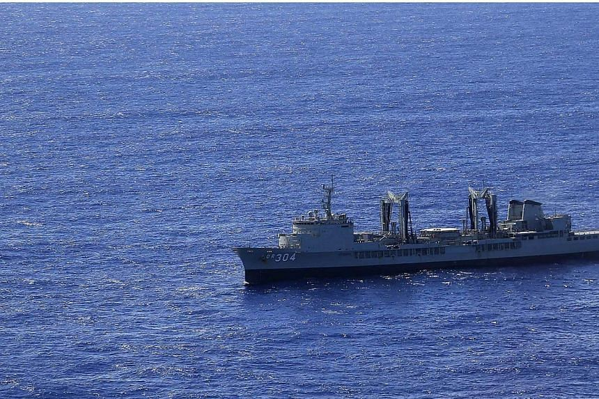 A small search boat sits in front of the Australian Navy ship HMAS Success as a Royal New Zealand Air Force P3 Orion maritime search aircraft flies over it in the southern Indian Ocean as they look for debris from missing Malaysian Airlines flight MH