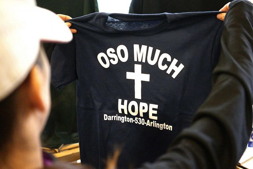 31162635onMs April Clark looks at a new Oso mudslide support t-shirt in the Action Sports shop in downtown Arlington, Washington, on March 28, 2014. -- FILE PHOTO: REUTERS