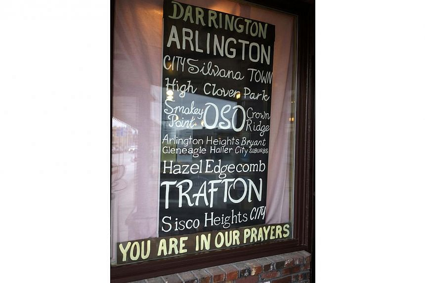 A sign referring to mudslide victims in nearby Oso is seen at a shop in downtown Arlington, Washington, on March 28, 2014. -- FILE PHOTO: REUTERS