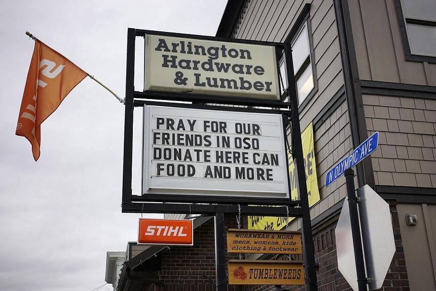 A sign referring to mudslide victims in nearby Oso is seen outside a store in downtown Arlington, Washington, on March 28, 2014. -- FILE PHOTO: REUTERS
