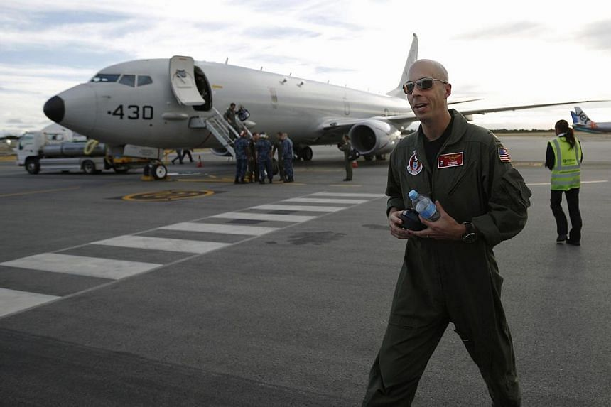 A U.S. Navy P8 Poseidon aircraft pilot, Lt Commander David Mims is pictured in front of the plane upon his return from a search flight for Malaysia Airlines flight MH370 over the Indian Ocean, at Perth International Airport on March 31, 2014. Of