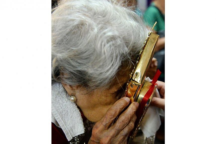 A Roman Catholic woman from the Philippines kisses one of the relics of the late Pope John Paul II at a chapel in Manila on April 1, 2014. -- PHOTO: AFP