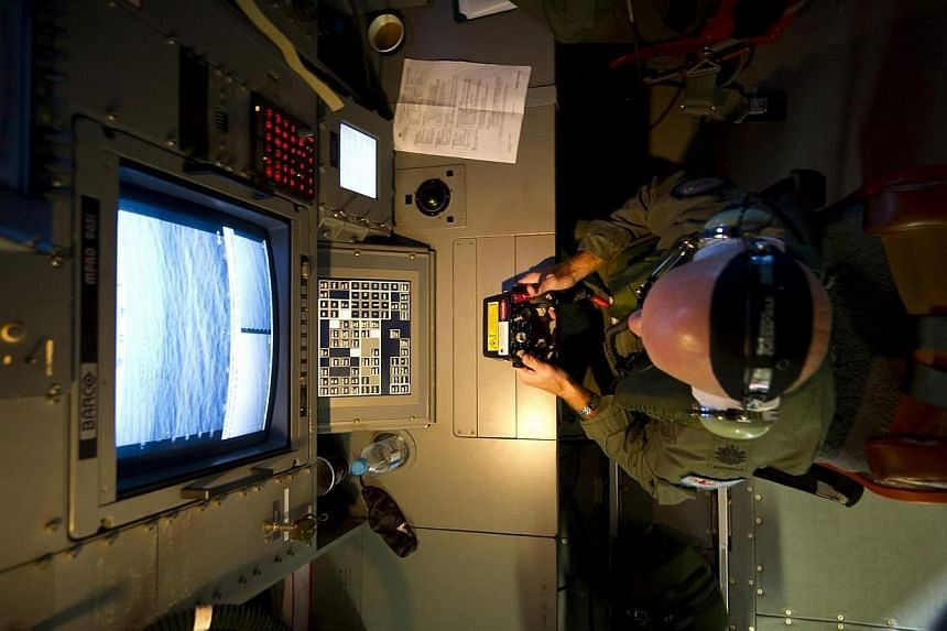 Royal Australian Air Force (RAAF) Warrant Officer Michael Wright uses the advanced optical systems aboard a RAAF AP-3C Orion aircraft during the search in the southern Indian Ocean for debris from the missing Malaysian Airlines flight MH370, in this