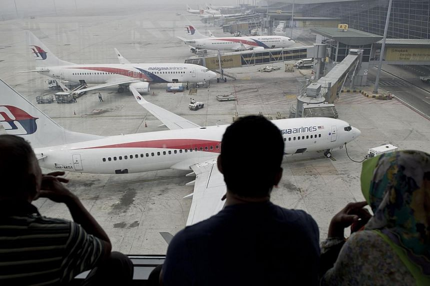 Passengers watch Malaysia Airlines planes on the tarmac at Kuala Lumpur International Airport (KLIA) in Sepang on March 13, 2014.Captain of a Chinese vessel searching for the missing Malaysia Airlines flight has said nothing has been found rela