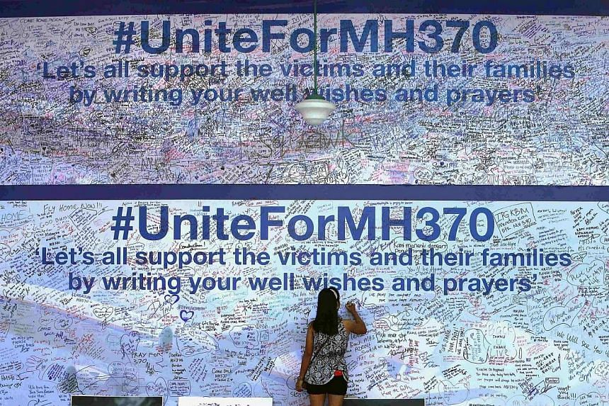 A woman writes a message on a board dedicated to passengers onboard the missing Malaysia Airlines Flight MH370 and their family members, in Petaling Jaya on March 19, 2014.Just 43 per cent of Malaysians are satisfied with their government's han