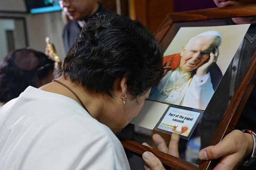 A Roman Catholic woman from the Philippines touches a skullcap, one of the relics of the late Pope John Paul II, on display at a chapel in Manila on April 1, 2014. -- PHOTO: AFP