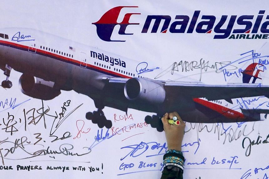A woman writes a message on a board for passengers onboard missing Malaysia Airlines Flight MH370 and their family members, at Dataran Merdeka in Kuala Lumpur on March 22, 2014.The Malaysian authorities released the transcript of the final comm