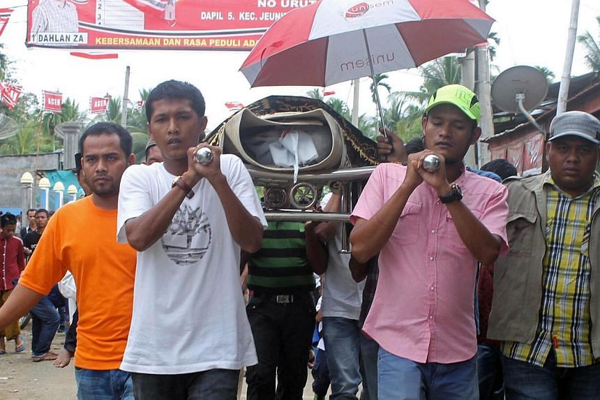 Supporters carry the dead body of an Aceh Party supporter during a funeral in Biruen, Aceh province on Tuesday, April 1, 2014, who was killed after two men on a motorcycle opened fire on a small van decorated with pictures of election candidates from