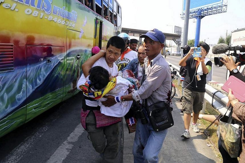 Anti-government protesters carry a comrade who was shot as their bus came under fire in Bangkok on Tuesday, April 1, 2014.A Thai anti-government demonstrator was shot dead and four others injured on Tuesday, an emergency official said, when uni