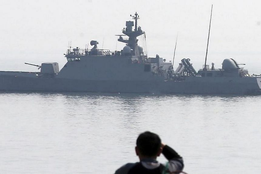 A man looks at a South Korean naval vessel in the sea off Daecheongdo, an island near the border with North Korea on Tuesday, April 1, 2014.An unmanned drone crashed on a South Korean island near disputed maritime border with North Korea, Yonha