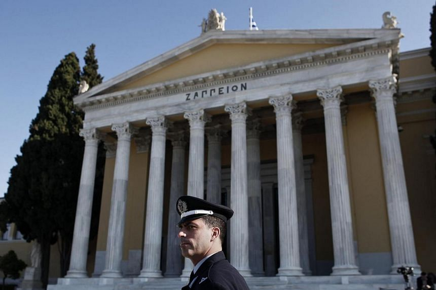 A police officer stands in front of the Zappeion during an European Union Finance Ministers informal meeting in Athens on Tuesday, April 1, 2014.Greece will receive 6.3 billion euros (S$10.9 billion) from its pending EU bailout fund at the end