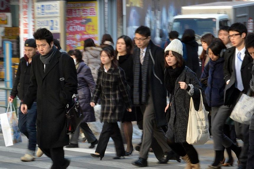 Businessmen and women cross a road in Tokyo on Feb 17, 2014. Japan is considering expanding a controversial program that now offers workers from China and elsewhere permits to work for up to three years, as the world's fastest-aging nation scr