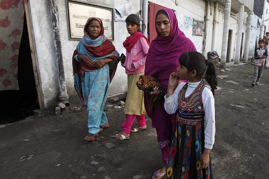 Sobia Sawan (second right), wife of of Pakistani Christian man Sawan Masih, walks with her daughters Noor (right) and Romika (third right), outside her house in Lahore on March 28, 2014.A Pakistani man sentenced to death for blasphemy appealed