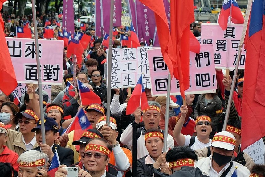People wave national flags and placards as they demonstrate to support the government and a controversial Taiwan-China trade pact in Taipei on Tuesday, April 1, 2014.Hundreds of Taiwanese protesters who support a controversial trade pact with C