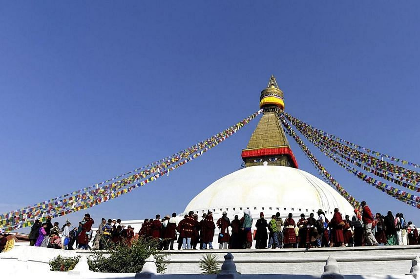 In this photograph taken on Feb 13, 2013, Buddhist devotees gather the Boudhanath Stupa - close to where a monk self-immolated later in the day against Chinese rule in Tibet - on the third day of Losar, the Tibetan new year, in Kathmandu. Tibeta