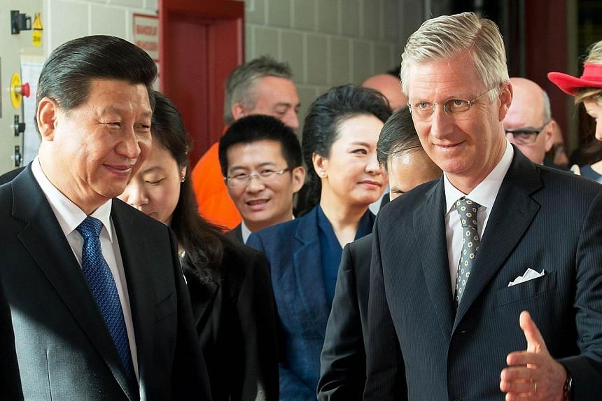 Chinese President Xi Jinping and King Philippe of Belgium discuss during a visit of car manufacturer Volvo Cars in Ghent on April 1, 2014. Winding up an 11-day visit to Europe taking in mega business deals and stately banquets, President Xi Jinp