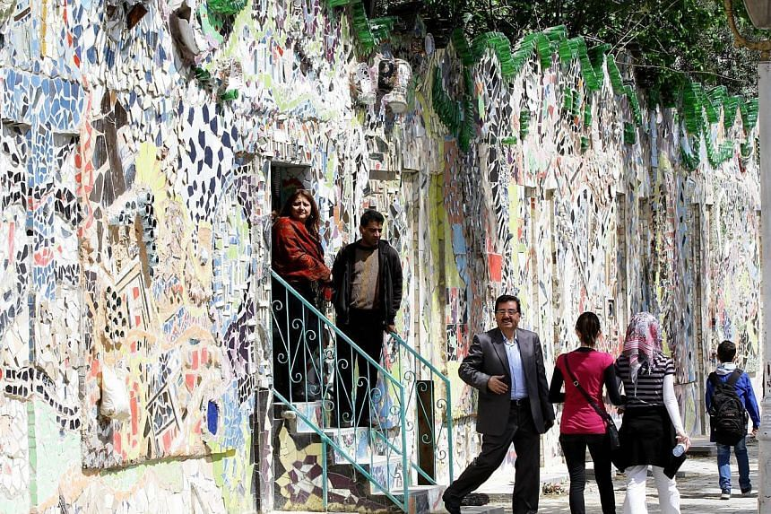 Syrians walk through a decorated wall that won the Guinness World Records award for the largest mural made from recycled material, in Damascus's al-Mazzeh neighborhood on March 31, 2014 . -- PHOTO: AFP